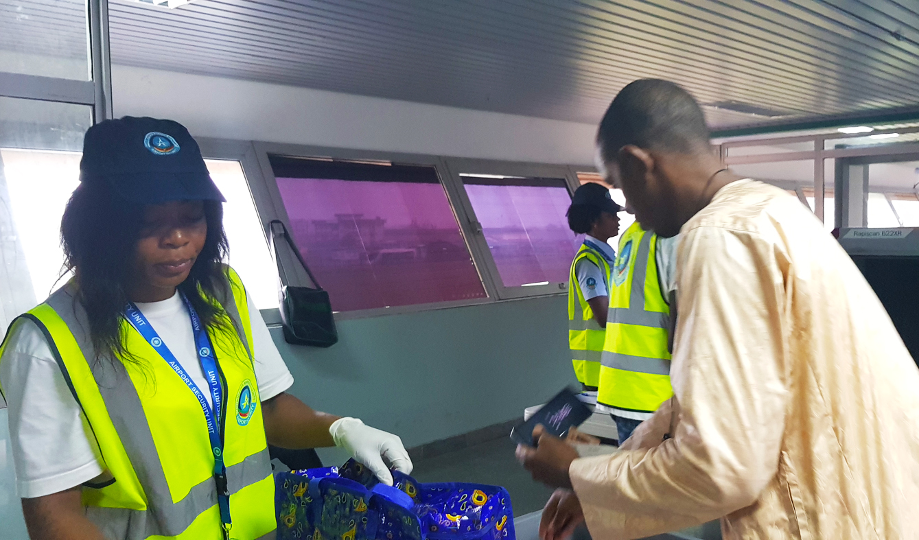 Search of passengers' hand luggage by newly assigned airport security officers at Douala International Airport following the switch of the implementation of security measures at the airport.